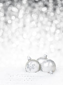 White baubles on sheet notes against defocused light background