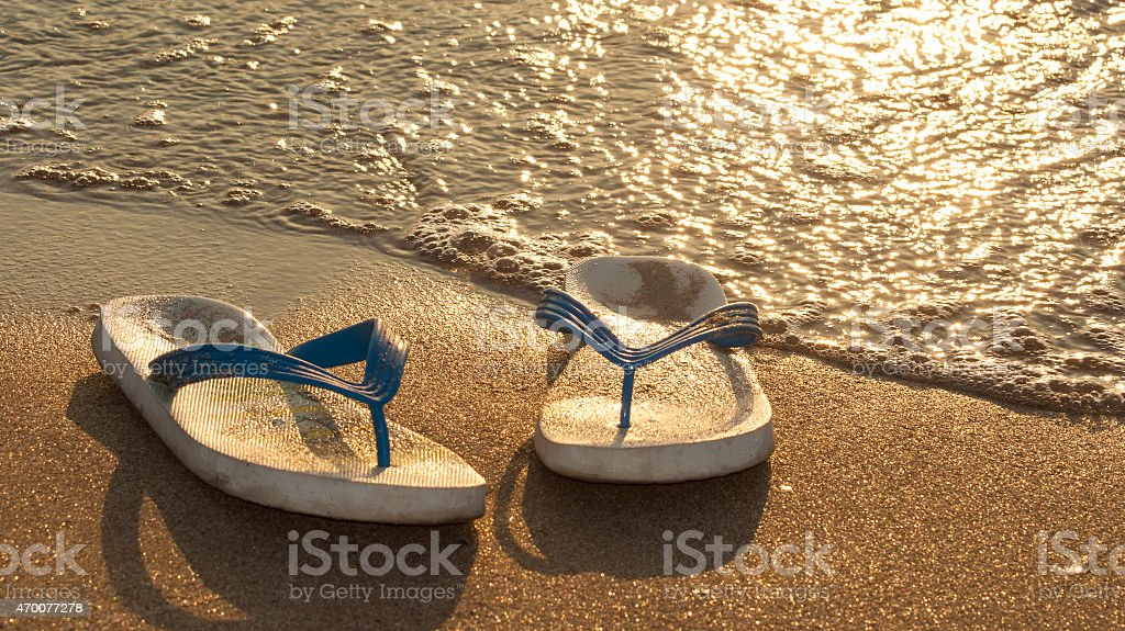 White beach slippers on the sand stock photo