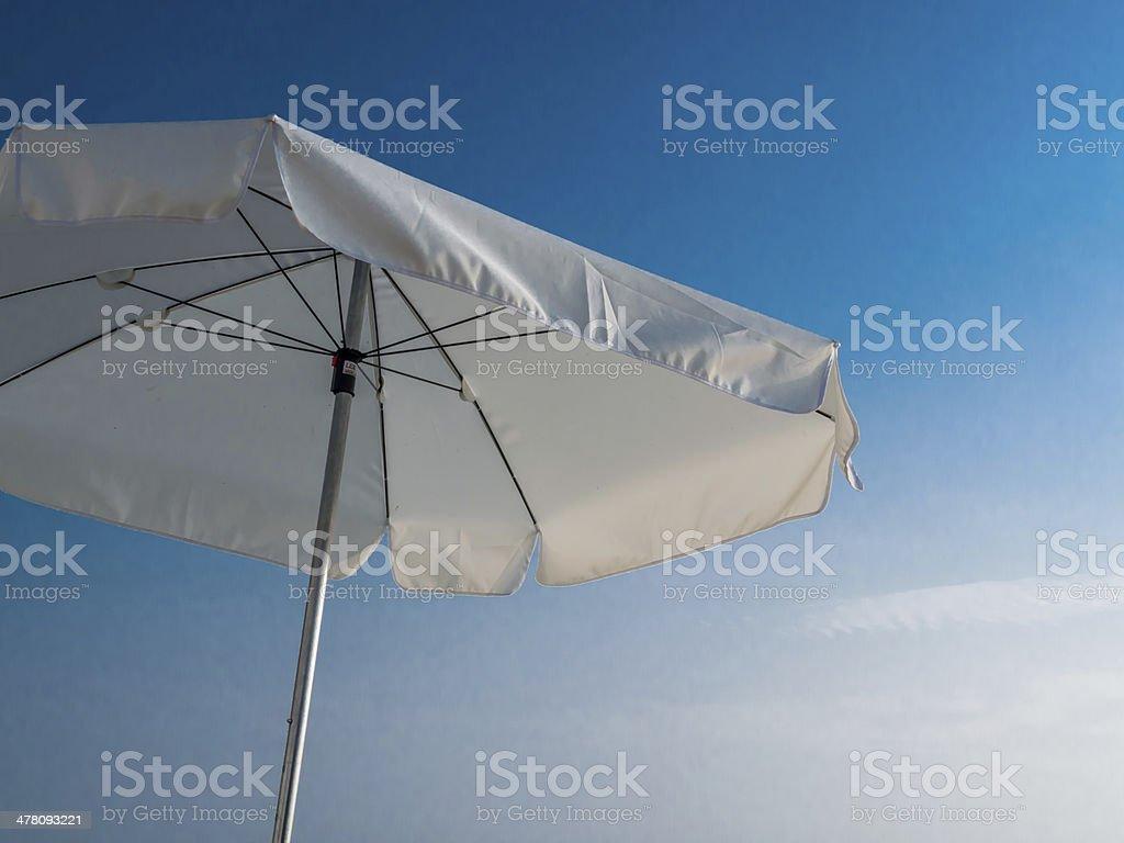 White beach umbrella with a blue summer sky stock photo