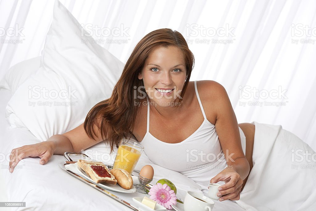White bedroom: Young woman having luxury breakfast in bed royalty-free stock photo