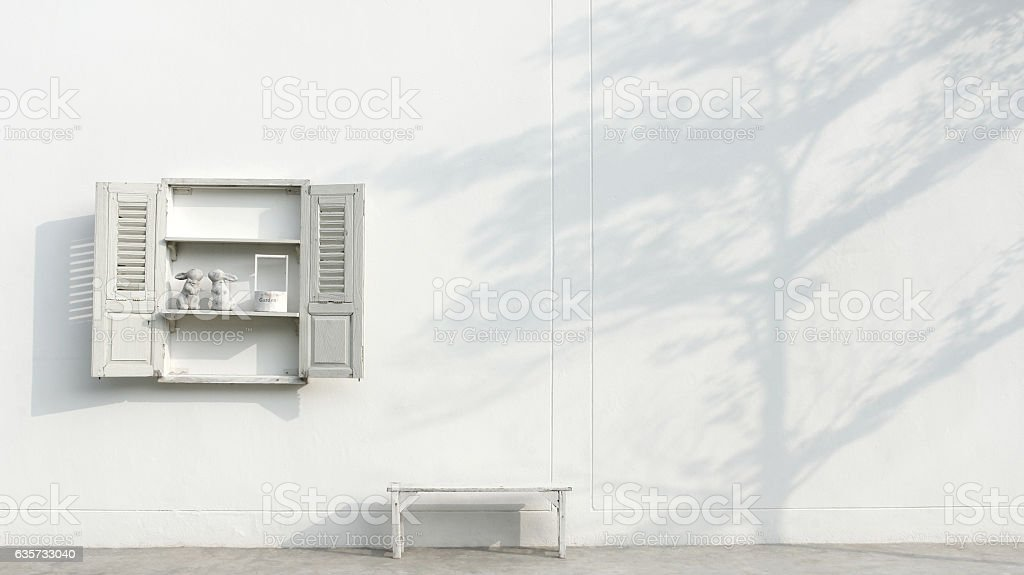 White bench and window and shadow branch tree on wall stock photo