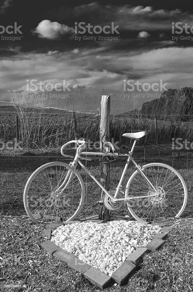 white bike attached to a fence with heart shape rocks stock photo