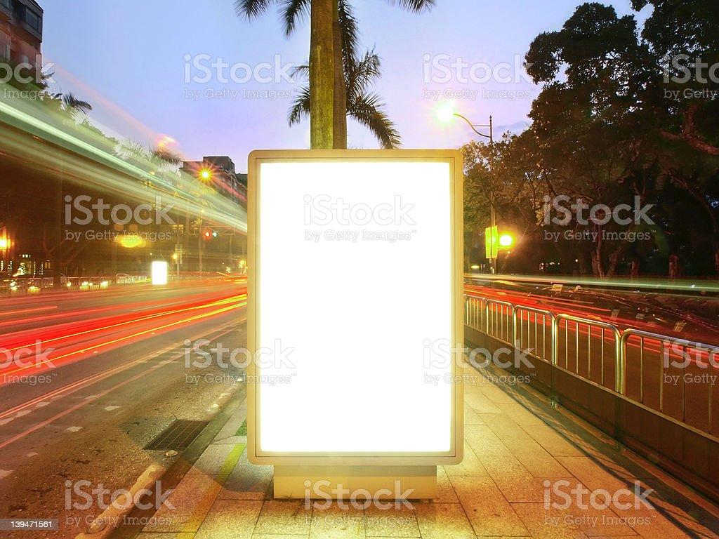 White billboard screen on sidewalk next to blurred traffic stock photo