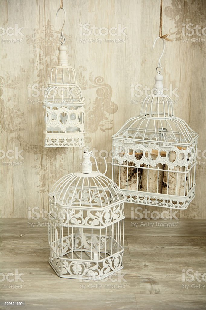 White birdcages in the interior wall with an ornament stock photo