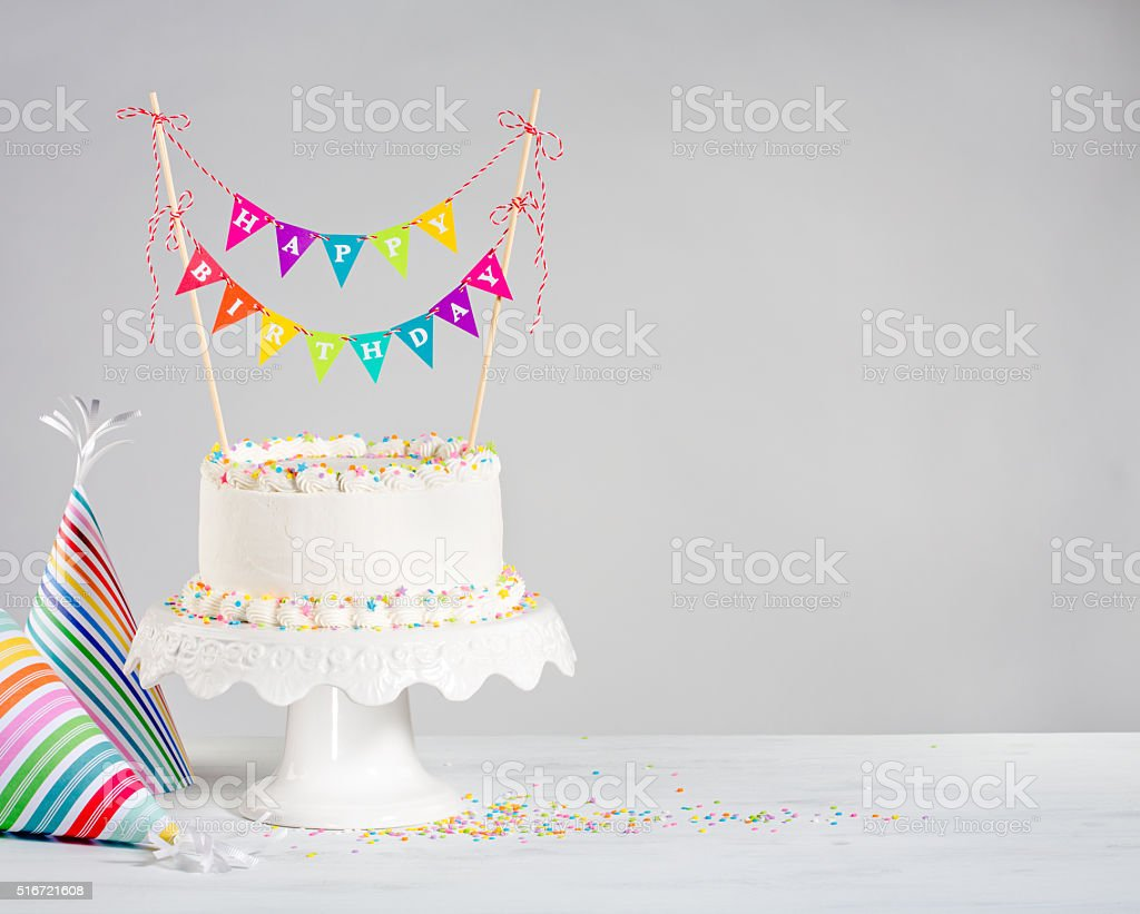 White Birthday Cake colorful bunting stock photo