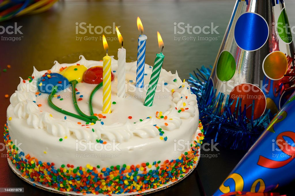 A white birthday cake with colorful sprinkles and balloons  royalty-free stock photo