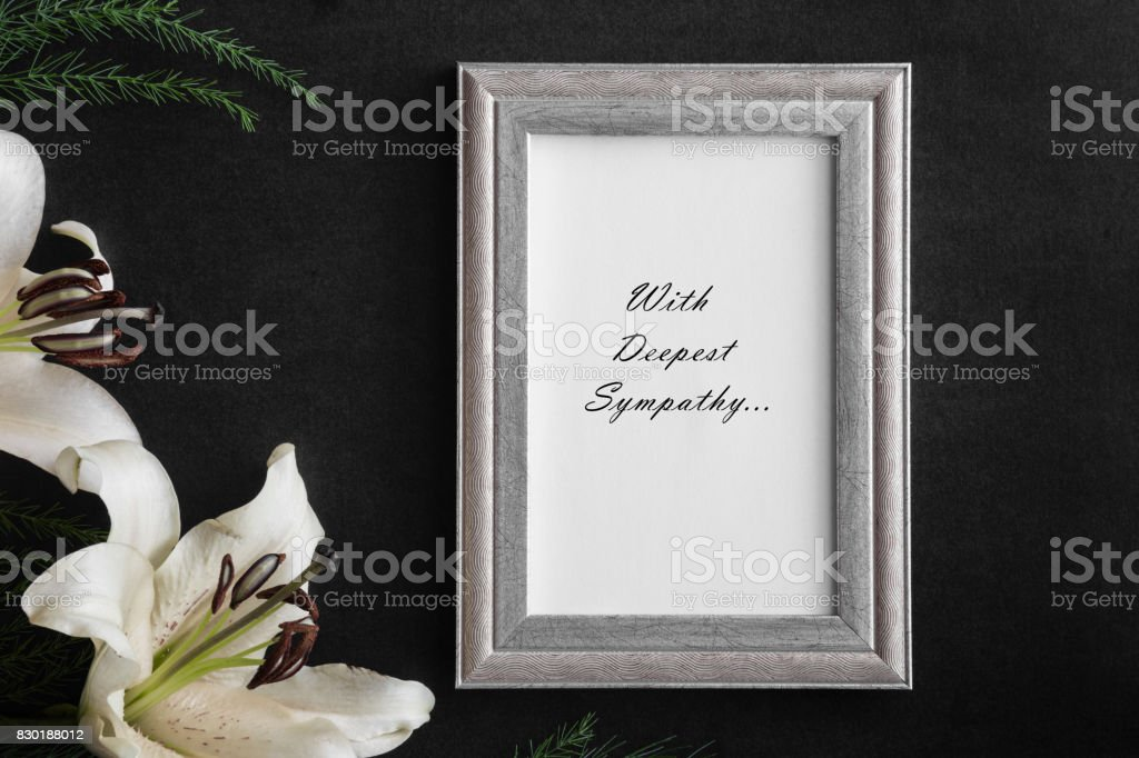 White blank condolence card with text in the frame. Lily flowers on...