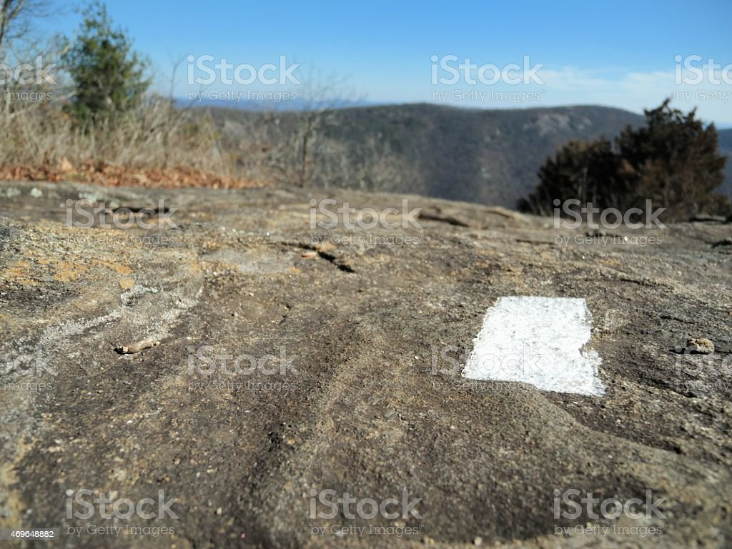 White blaze appalahcian trail marker on rock ground stock photo
