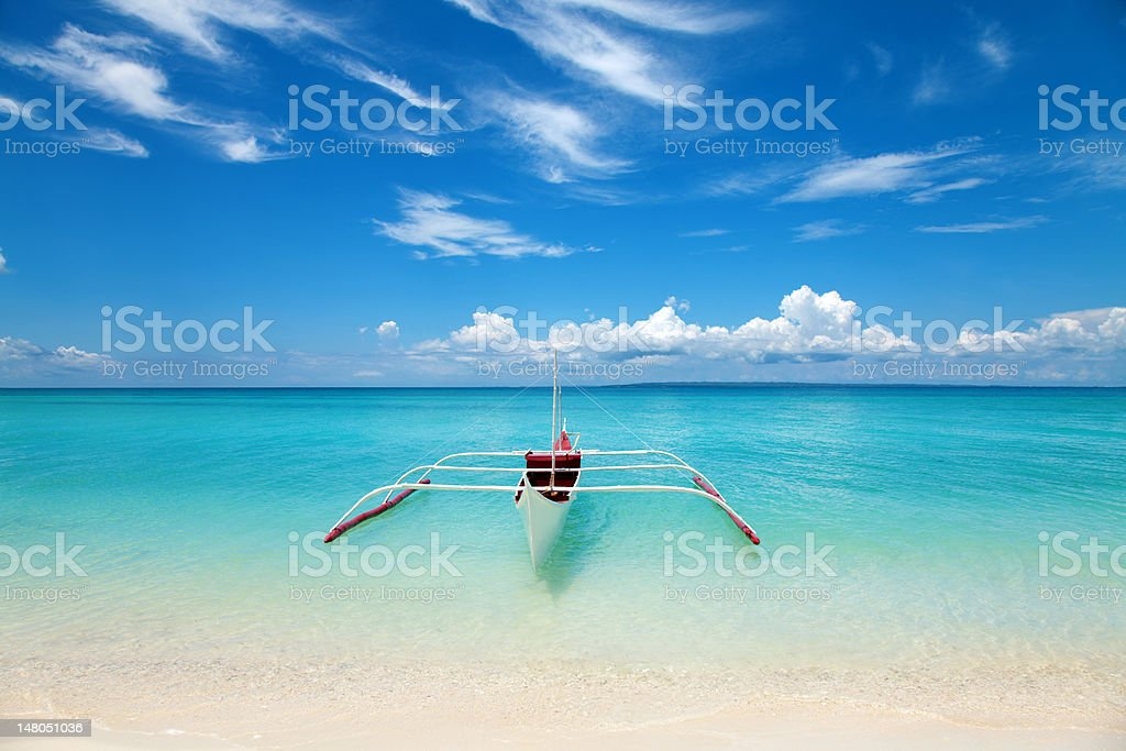 White boat in turquoise water on a tropical beach stock photo