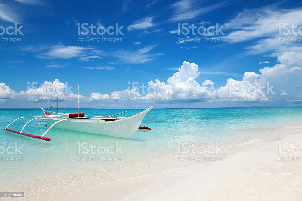 White boat on a tropical beach stock photo