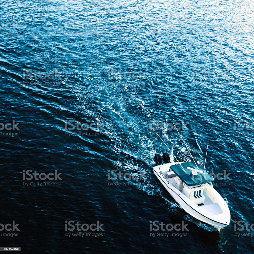 White boat on beautiful dark blue waters stock photo