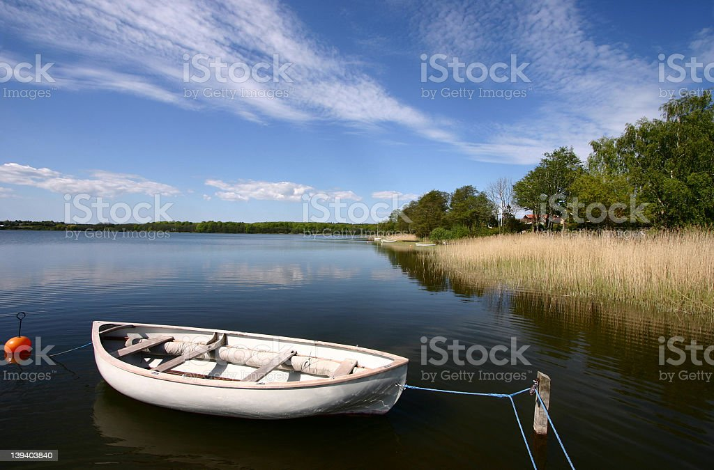 A white boat tied to a stick in a clear lake royalty-free stock photo