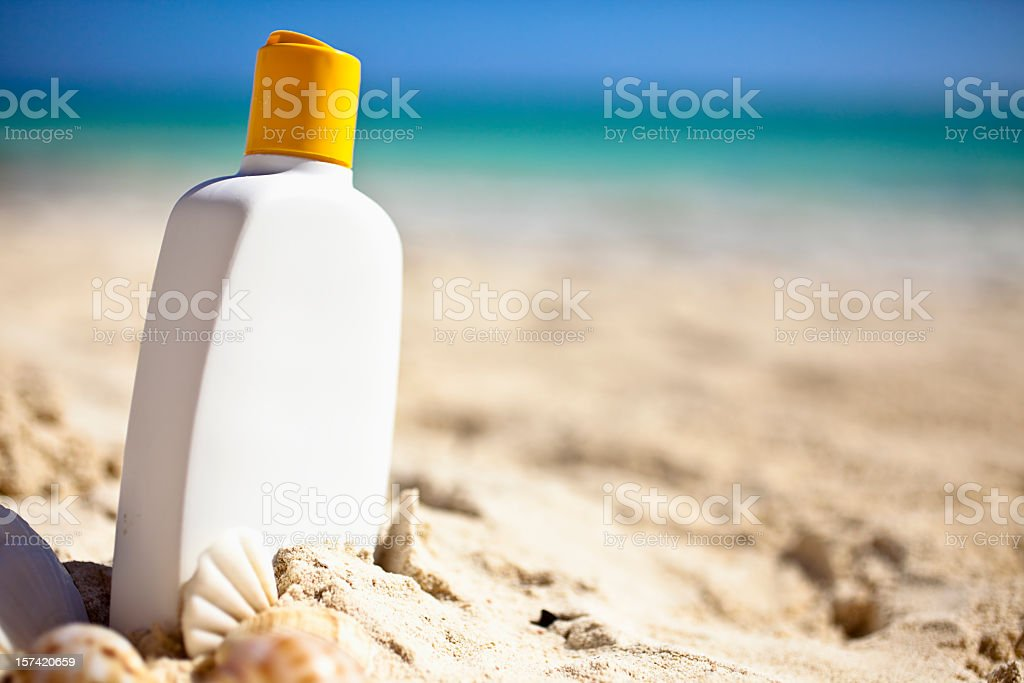 White bottle of sunscreen resting in the sand at the beach stock photo