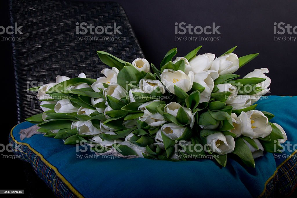 White bouquet of tulips on black chair with blue cushion royalty-free stock photo
