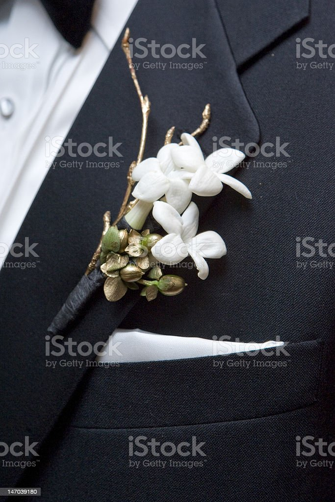 White boutonniere flowers attached to suit jacket royalty-free stock photo