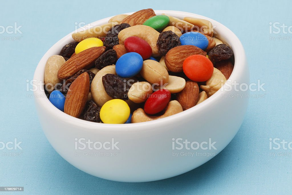 White bowl filled with trail mix on blue background stock photo