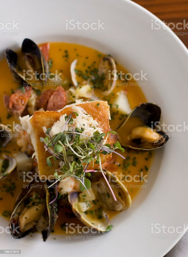 White bowl filled with various seafood in a broth  royalty-free stock photo