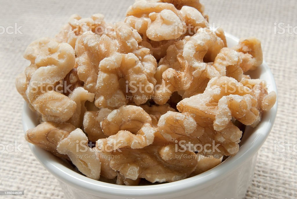 white bowl full of shelled walnuts with a burlap background royalty-free stock photo
