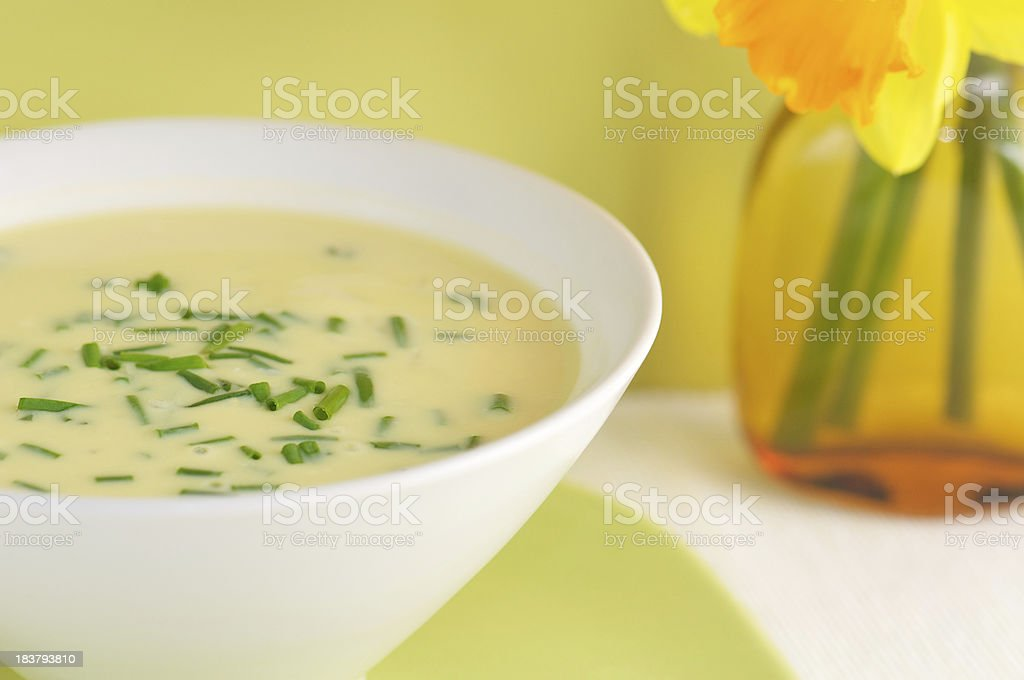 White Bowl of Avgolemono Soup with Daffodils royalty-free stock photo