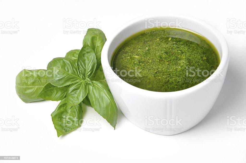 White bowl of basil pesto with fresh basil leaves on left stock photo