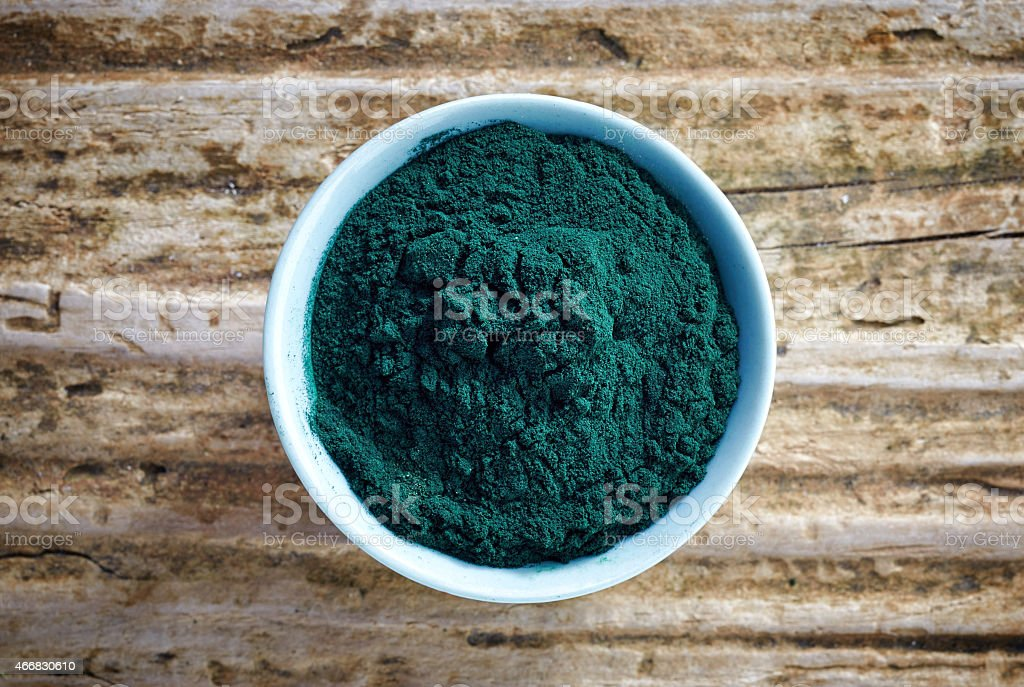 White bowl of dark green spirulina algae powder stock photo