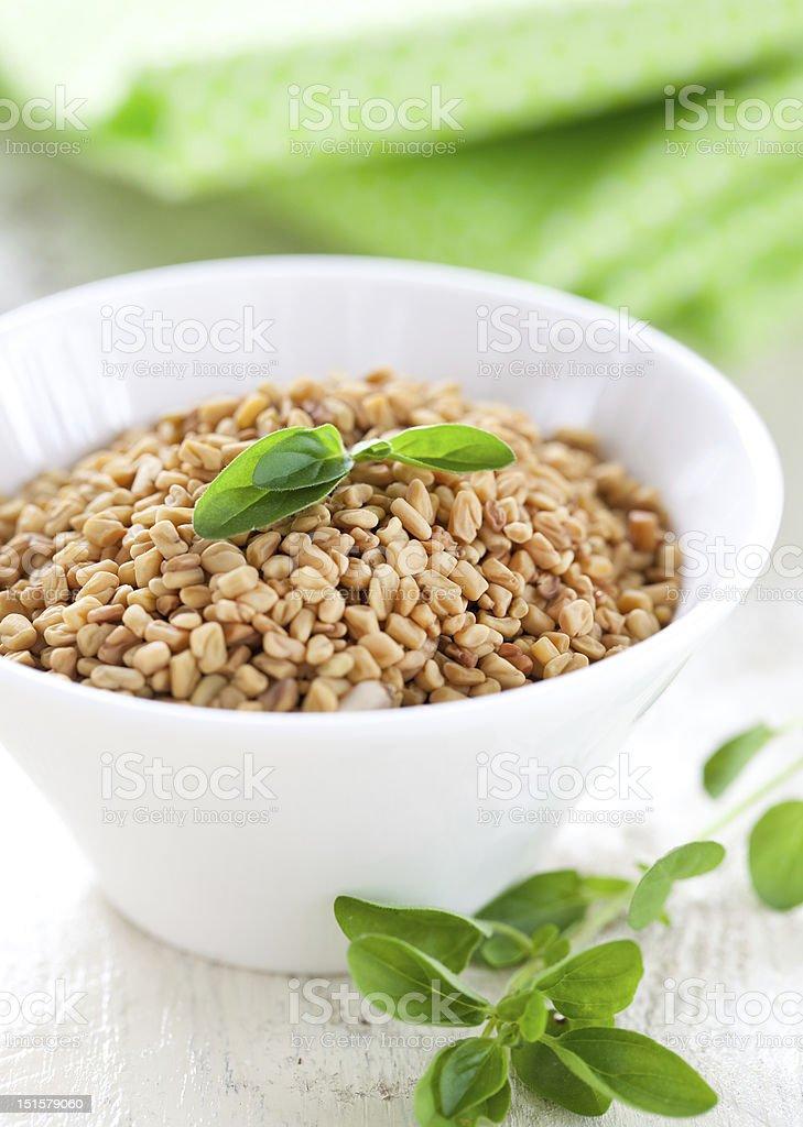 White bowl of fenugreek with herbs stock photo