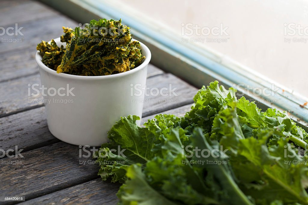 White bowl of kale chips next to fresh kale by the window stock photo