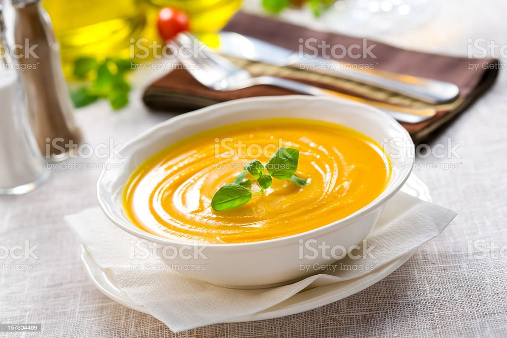 White bowl of pumpkin soup with garnish stock photo