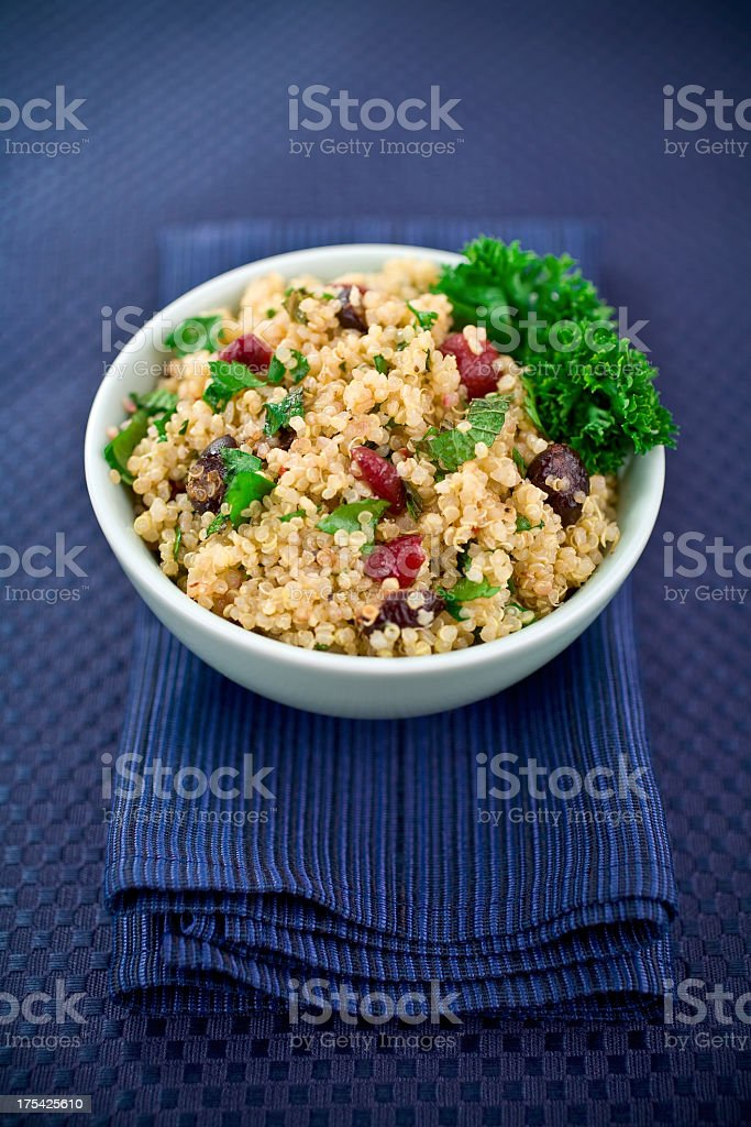 White bowl of Quinoa Salad resting on a thick blue napkin stock photo