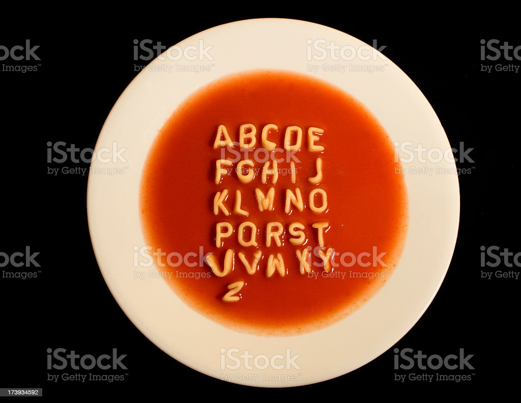 White bowl of soup with alphabet against black background stock photo