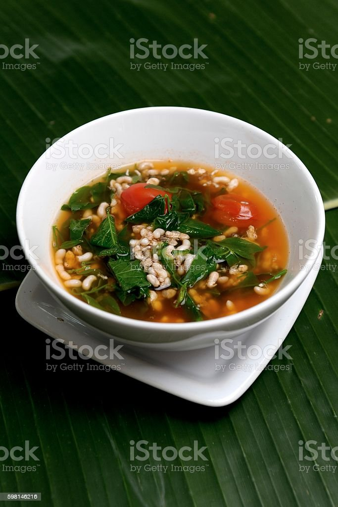 white bowl of spicy red ant eggs soup stock photo
