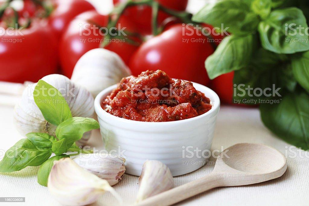 A white bowl of tomato sauce next to garlic stock photo