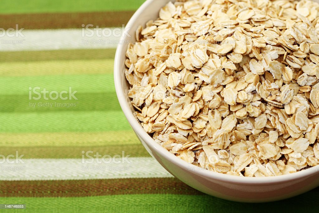 White bowl with oats on green towel royalty-free stock photo
