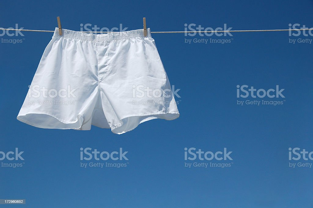 White boxer shorts clipped to clothesline against blue sky stock photo