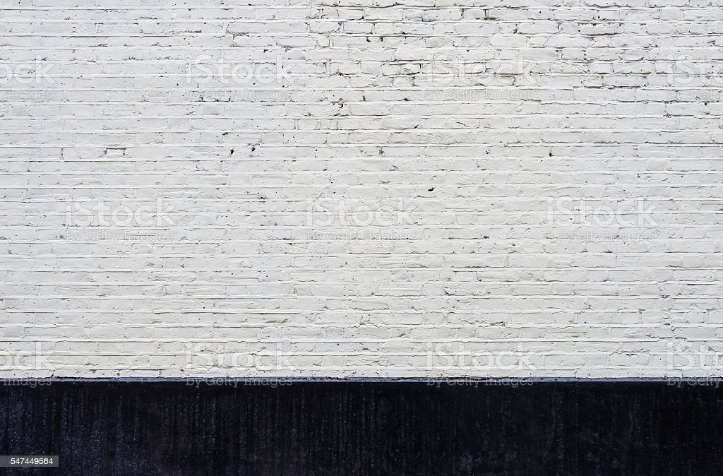 White brick wall and black skirting stock photo
