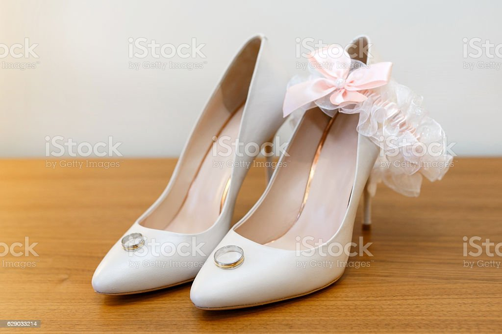 White bride's shoes, garter and wedding rings stock photo
