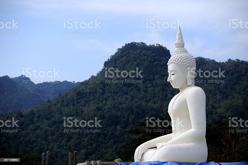 White buddha statue and blue sky background in Thailand. stock photo