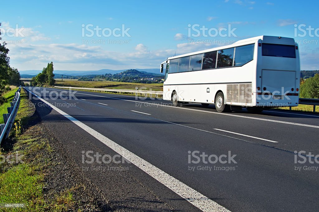 White Bus driving on an empty road in a landscape stock photo