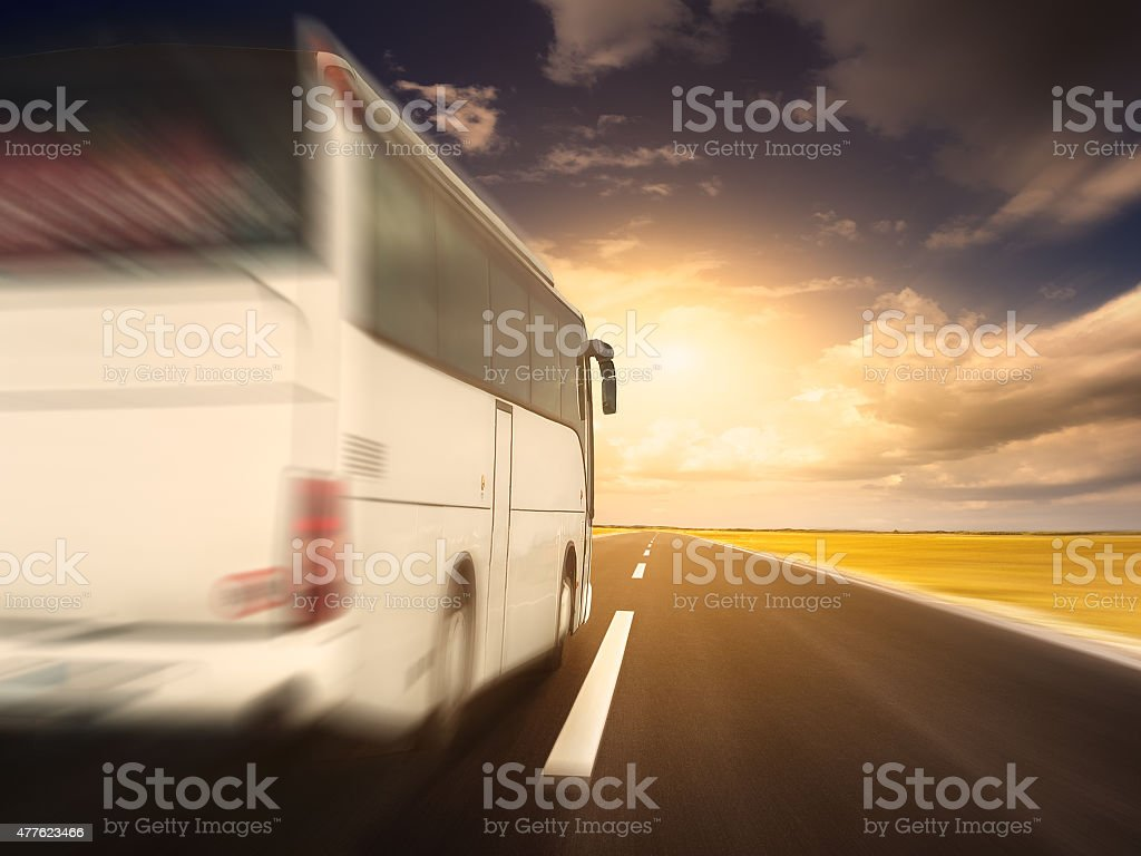 White bus in fast driving on an empty asphalt road stock photo