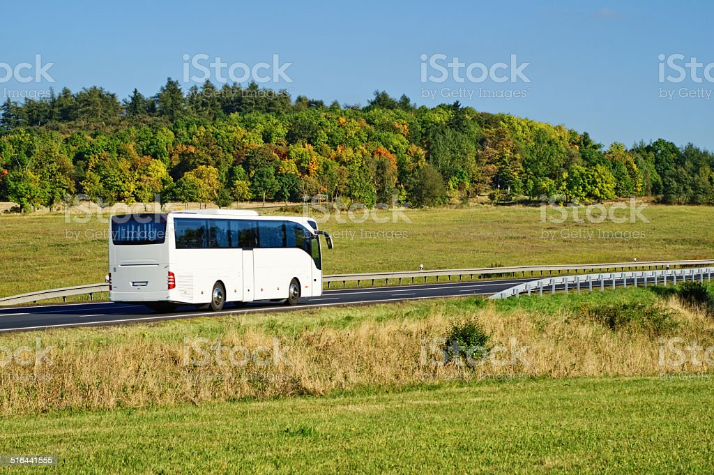 White bus on the road in the countryside stock photo