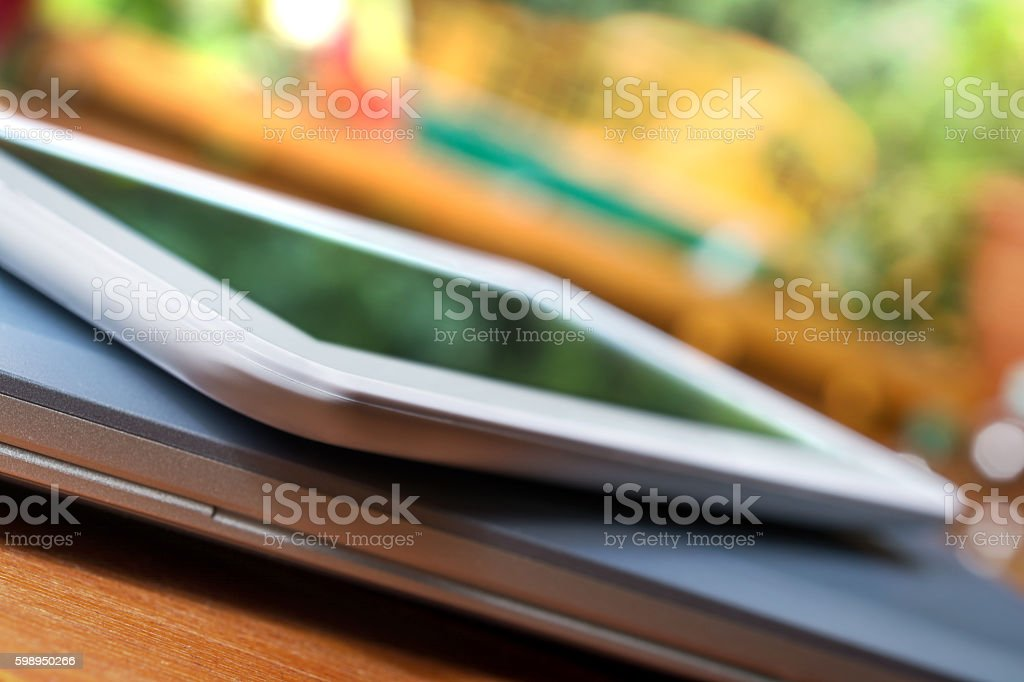 White Business Tablet Lying On Closed Notebook In Bright Atmosphere stock photo