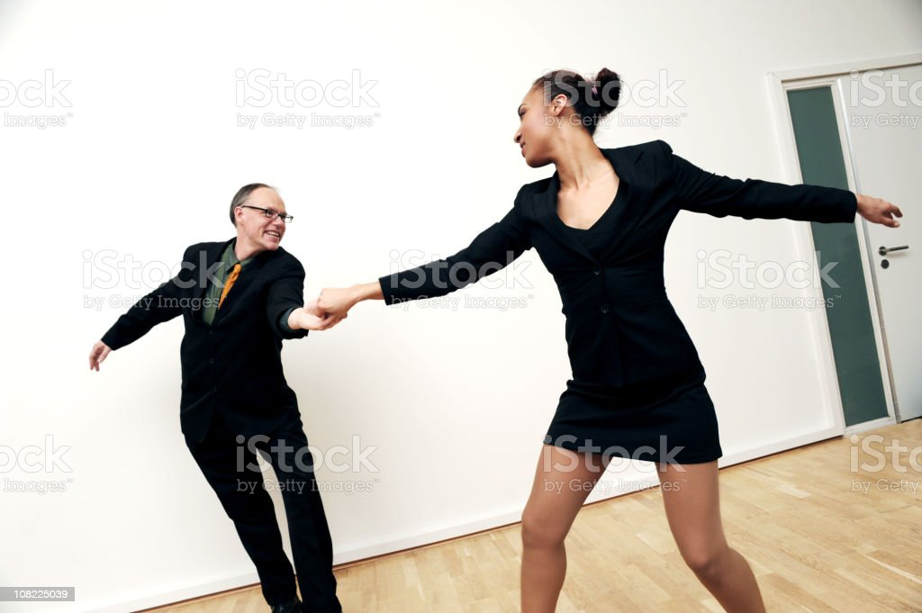 White Businessman and African American Businesswoman Dancing stock photo