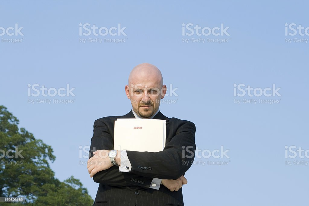 """White Businessman Outside Clutching File Marked """"SECRET"""" royalty-free stock photo"""