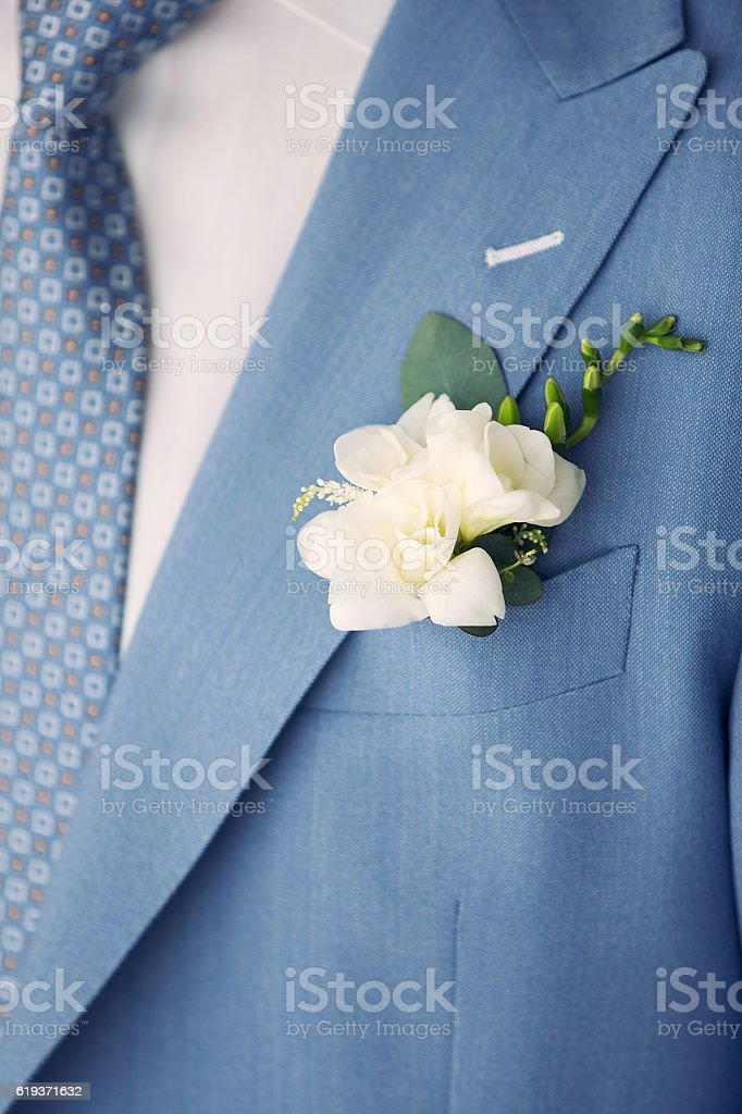 white buttonhole of the groom and blue suit stock photo