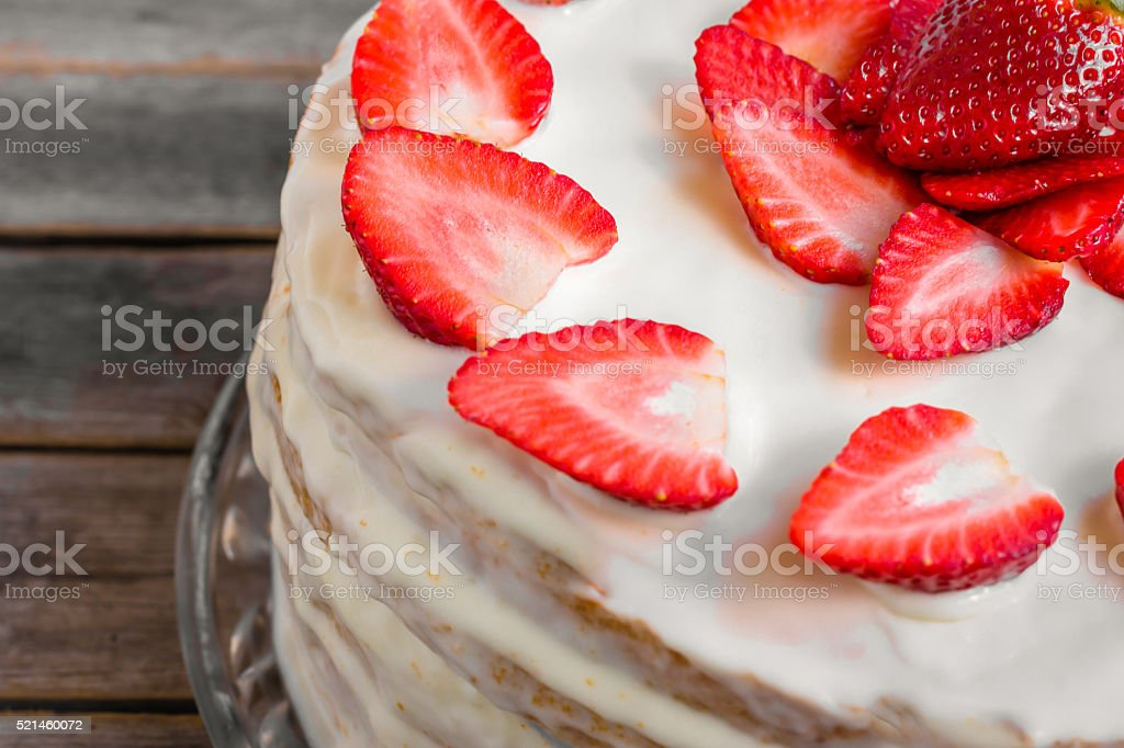White cake decorated with strawberries on a wooden table stock photo