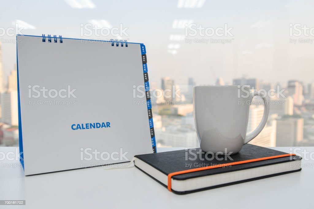 White Calendar and a cup of coffee and notebook on the white table stock photo