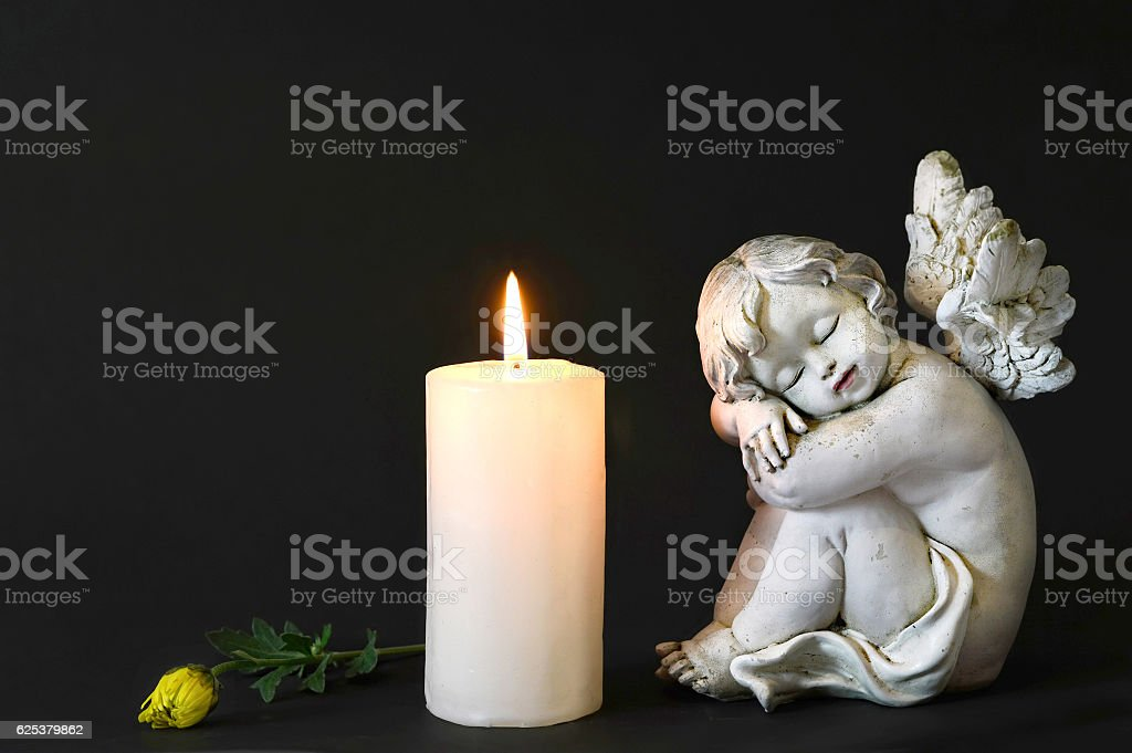 White candle, an angel and flower on dark background stock photo
