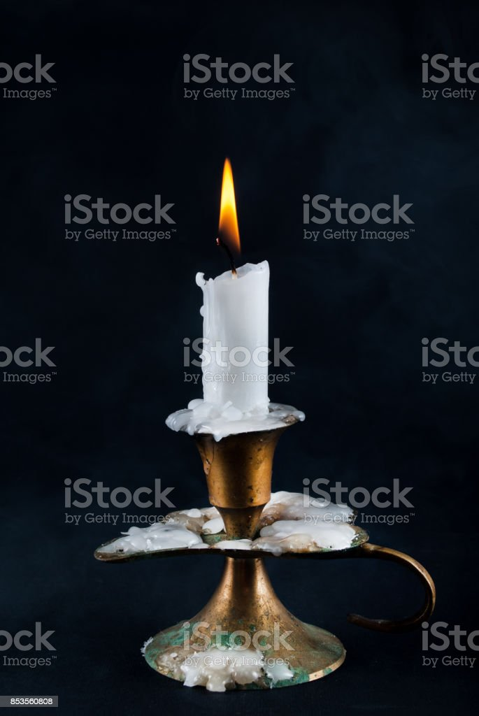 White candle burning in old candlestick and smoke in background stock photo