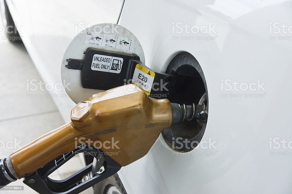 White car at gas station being filled with fuel stock photo