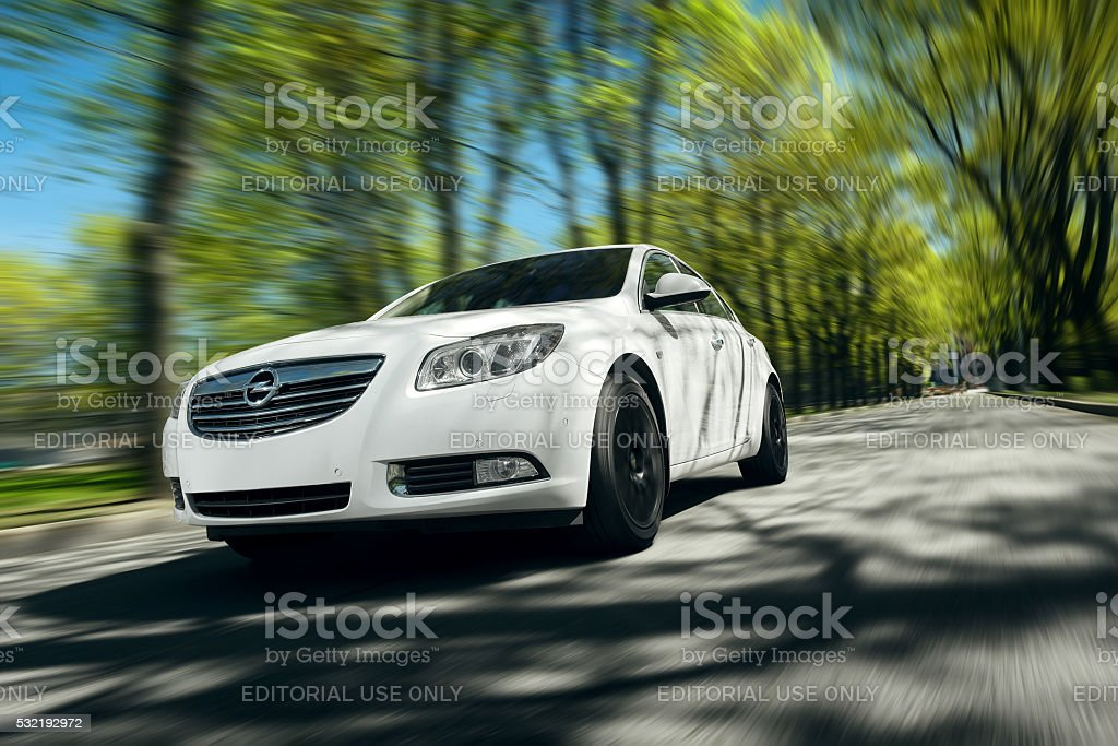 White car Opel Insignia drive on asphalt road at daytime stock photo